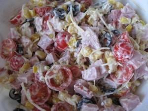 Готовый салат с маслинами, ветчиной и помидорами